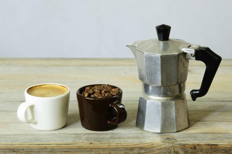 Two Cups Of Coffee And Beans And Percolator On Wood table