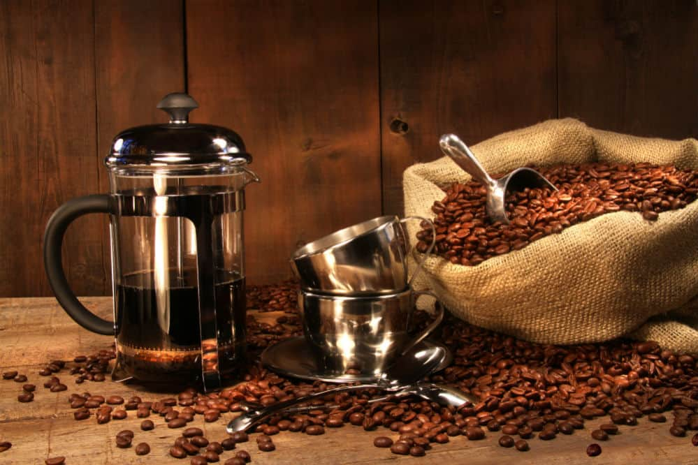 French Press Coffee Maker and coffee beans on brown sack