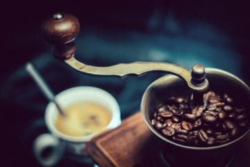 Coffee grinder with coffee beans and cup