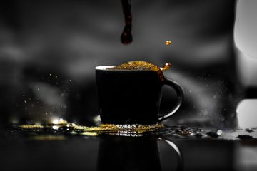 Coffee overflowing in black cup