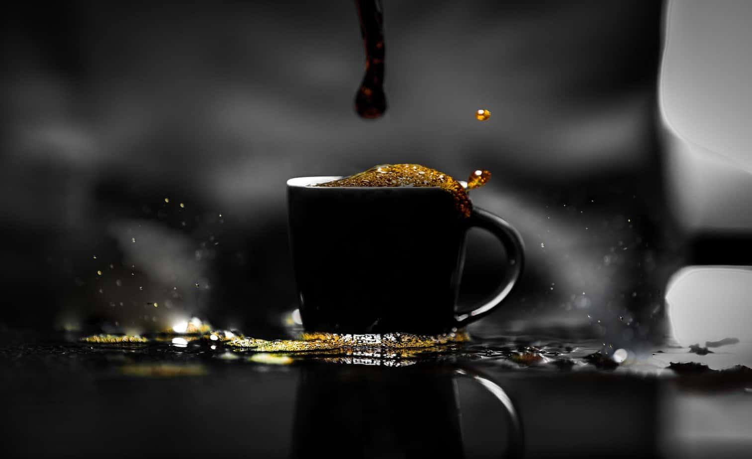 Coffee overflowing in black cup